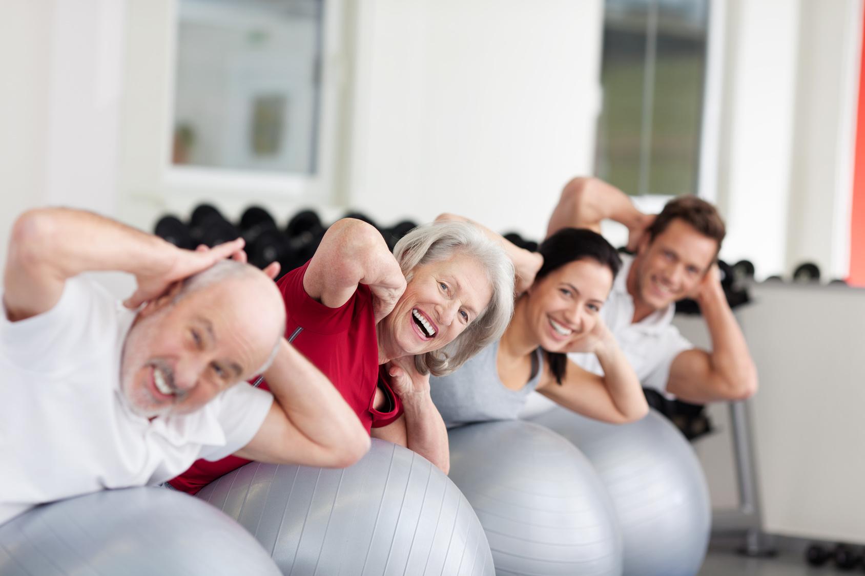 lachende ältere frau trainiert in der gruppe
